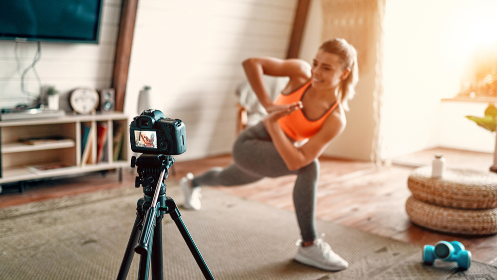 Fitness influencer filming herself doing a workout