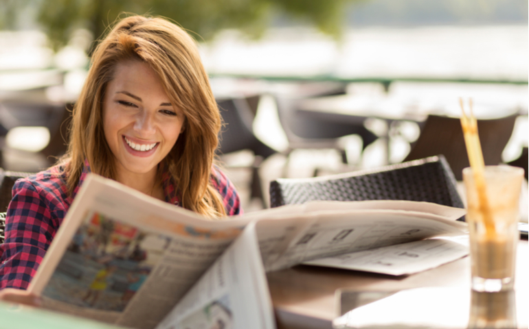 Woman smiling while reading newspaper in a outdoor cafe