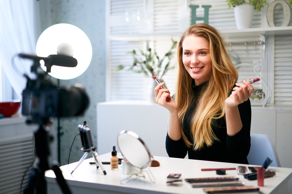 Beauty influencer holding up make up products while filming self on camera