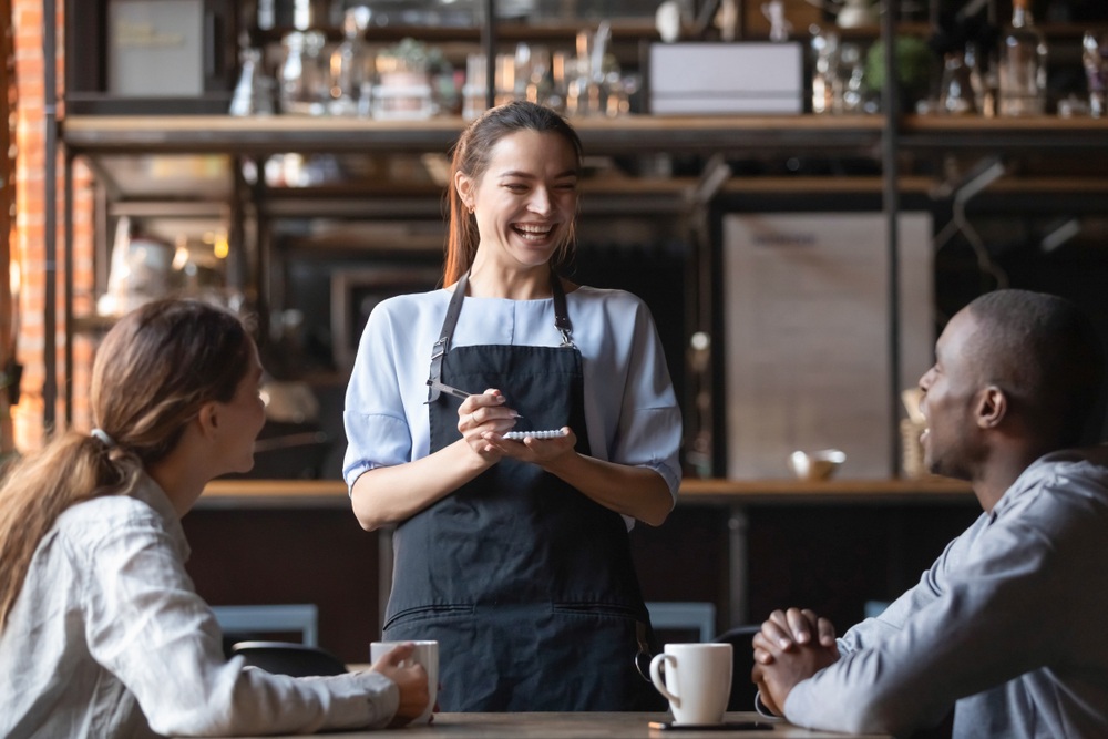 A waitress in a cafe, laughing with her customers